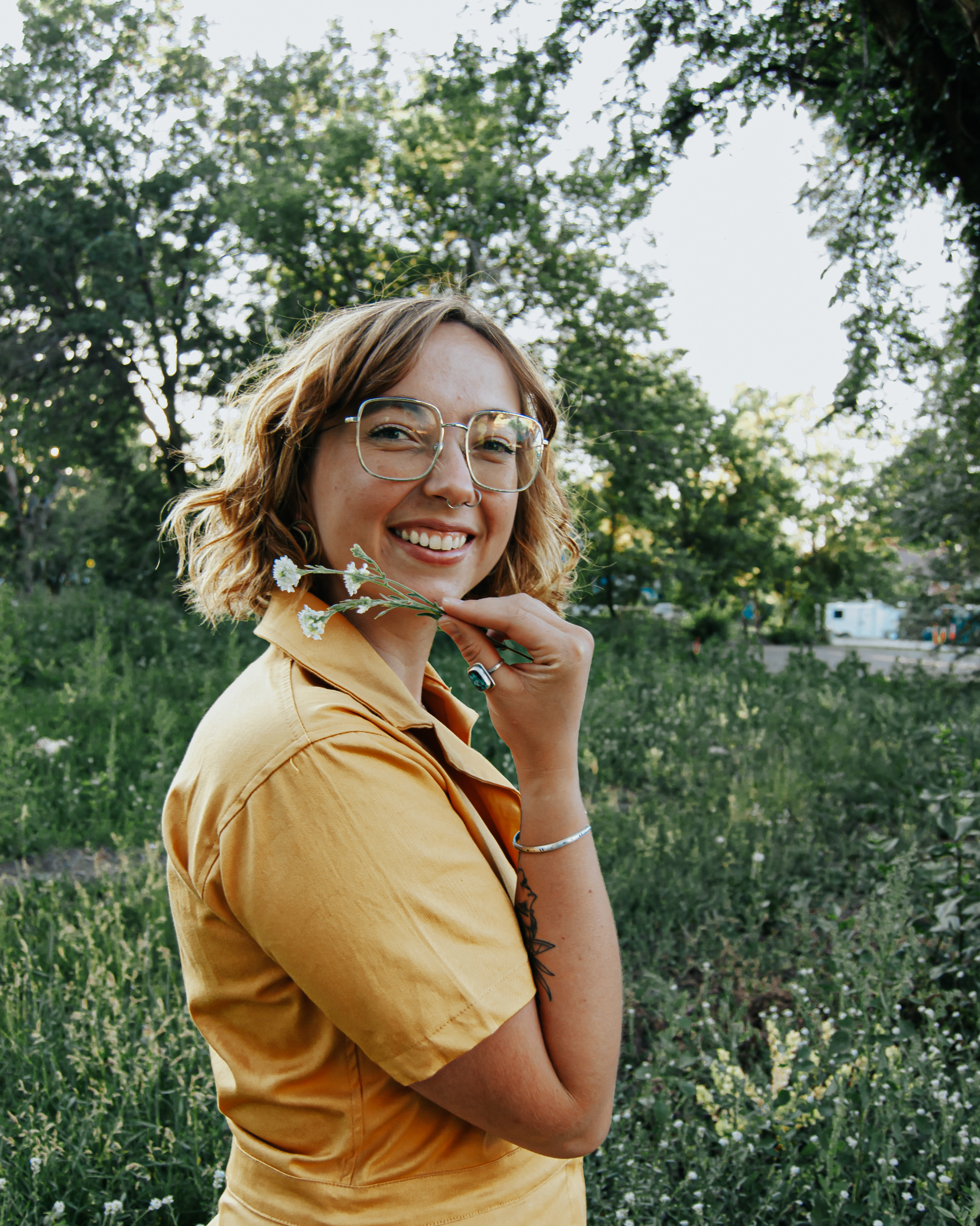 a photo of a woman (Anna) in a mustard yellow jumpsuit, from the waist up, turned to the side, with a bent arm, holding a flower below her chin. She has short curled, blonde-brown hair, on the lighter side. She wears oversized glasses with a thin silver rim. She has a cute nose that scrunches when she smiles, which she is doing. The background is a lush green field.